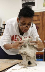 Easterseals client Willow Clark puts the finishing touches on her sculpture.