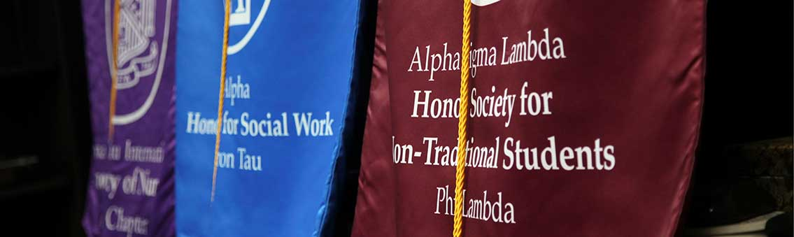honor society standards displayed at Thomas University commencement
